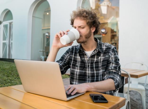 Junger mann, der seinen laptop in einem café benutzt