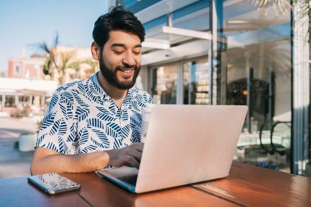 Junger mann, der seinen laptop in einer kaffeestube verwendet.