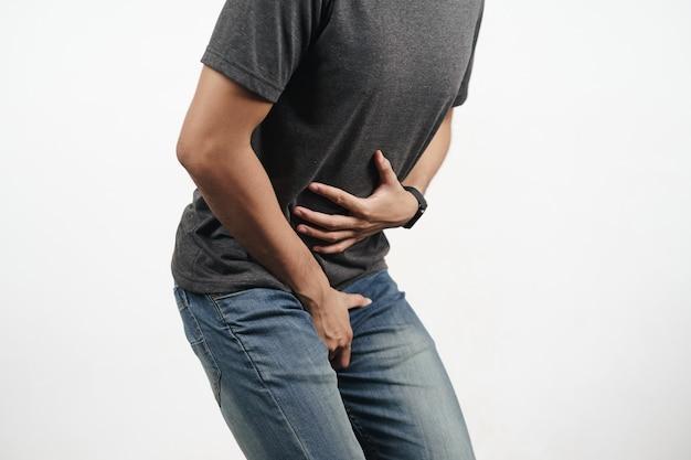 Junger mann, der seinen magen und schritt hält und an durchfall, inkontinenz, prostatitis, geschlechtskrankheiten leidet. gesundheitskonzept.
