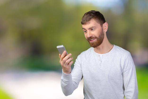 Junger mann, der seinen smartphone betrachtet