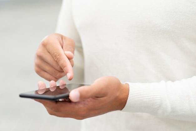 Junger mann, der seinen smartphone überprüft