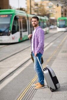 Junger mann, der seinen zug in der städtischen u-bahnstation wartet. lifestyle-konzept