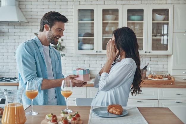 Junger mann, der seiner freundin beim frühstück in der heimischen küche eine geschenkbox gibt