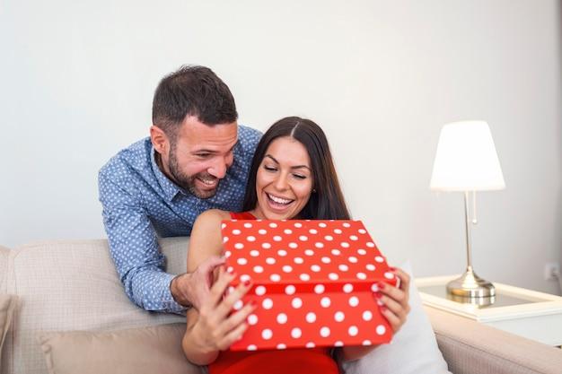 Junger mann, der seiner freundin eine geschenkbox gibt. valentinstag und menschen konzept - nahaufnahme des jungen paares mit geschenkbox zu hause