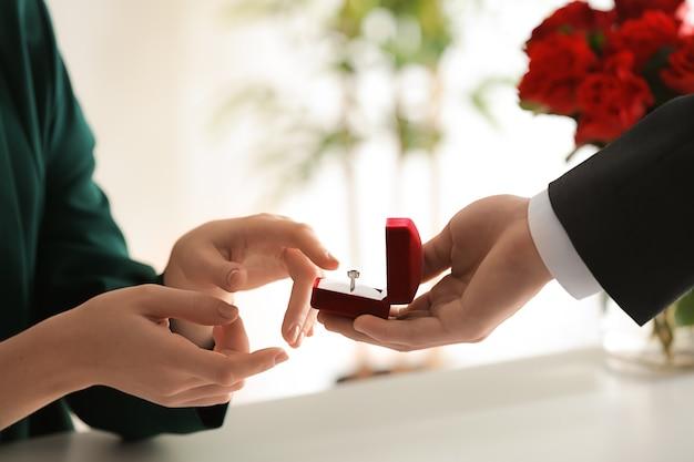 Junger mann, der seiner geliebten am romantischen datum vorschlägt