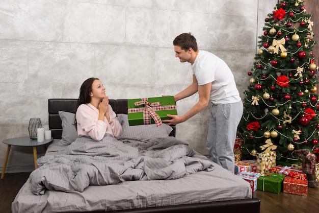 Junger mann, der seiner glücklichen freundin ein geschenk gibt, während sie auf einem bett sitzt und einen schlafanzug im schlafzimmer im loft-stil mit weihnachtsbaum mit vielen geschenken trägt