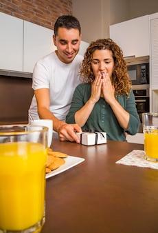 Junger mann, der seiner überraschten freundin eine geschenkbox gibt, während er in der heimischen küche frühstückt