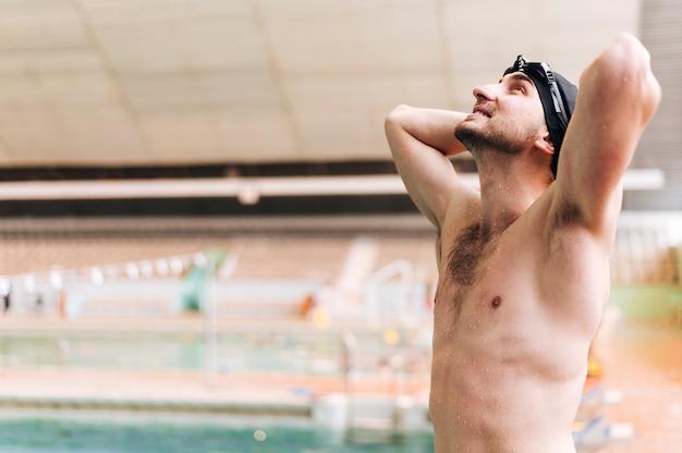 Junger mann der seitenansicht am swimmingpool, der oben schaut