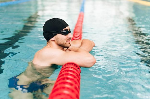 Junger mann der seitenansicht am swimmingpool