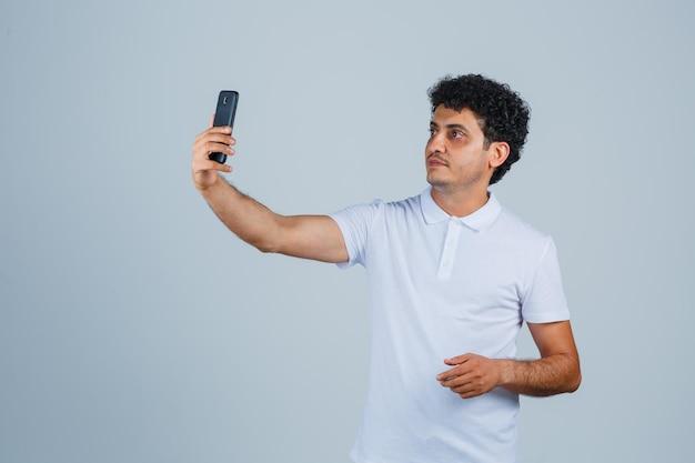 Junger mann, der selfie auf dem handy im weißen t-shirt macht und süß aussieht, vorderansicht.