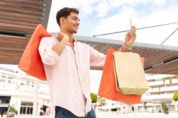 Junger mann, der selfie mit einkaufstaschen nimmt