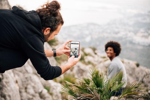 Junger mann, der selfie seines freundes sitzt auf dem berg nimmt