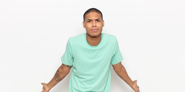 Junger mann, der sich ahnungslos und verwirrt fühlt, keine ahnung hat, absolut verwirrt mit einem dummen oder dummen blick