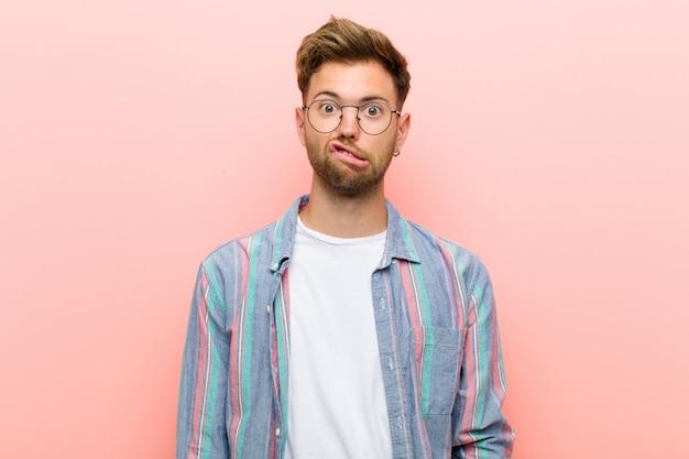 Junger mann, der sich ahnungslos, verwirrt und unsicher darüber fühlt, welche option er wählen soll, und versucht, das problem gegen die rosa wand zu lösen