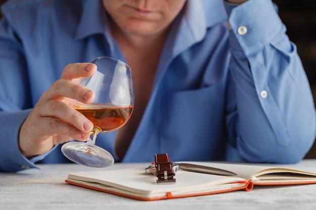 Junger mann, der sich allein fühlt und zu viel alkohol in seinem eigenen haus am tisch trinkt
