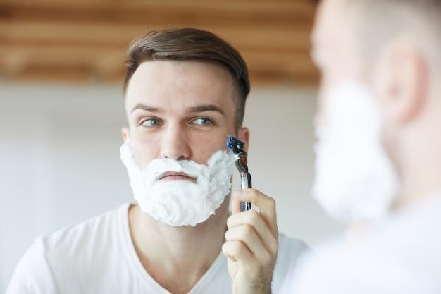 Junger mann, der sich am morgen rasiert