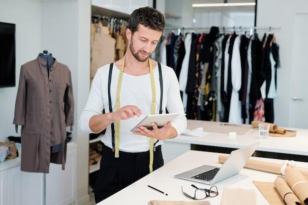 Junger mann, der sich auf das networking konzentriert, während er im touchpad blättert und durch neue modetrends schaut