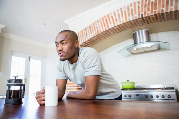 Junger mann, der sich auf dem tisch hält kaffeetasse lehnt