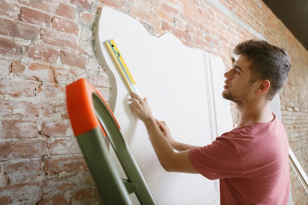 Junger mann, der sich auf die reparatur der wohnung selbst vorbereitet. vor renovierung oder renovierung. konzept der beziehungen, familie, diy. messen der wand vor dem malen oder entwerfen.