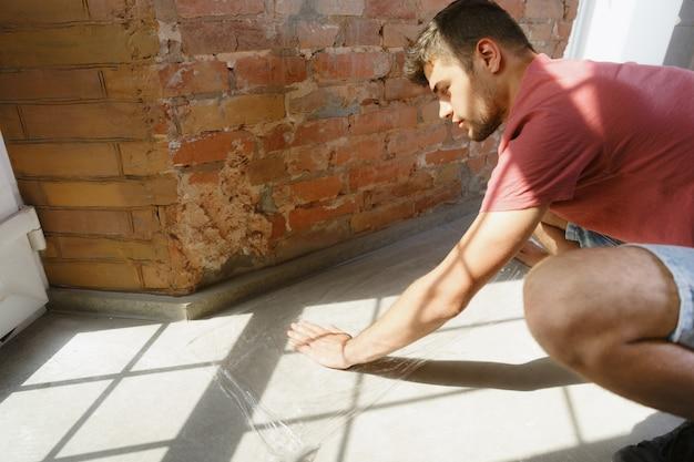Junger mann, der sich auf die reparatur der wohnung selbst vorbereitet. vor renovierung oder renovierung