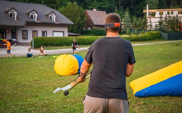 Junger mann, der sich auf einen angriff vorbereitet, während er bogenschießen-tag spielt