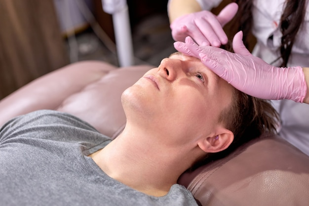 Junger mann, der sich auf massagetisch entspannt, der massage empfängt und massage auf spa-behandlung genießt.