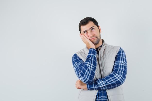 Junger mann, der sich auf seine offene handfläche in hemd, ärmelloser jacke stützt und nachdenklich aussieht. vorderansicht. platz für text