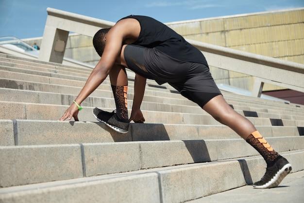 Junger mann, der sich auf treppen streckt