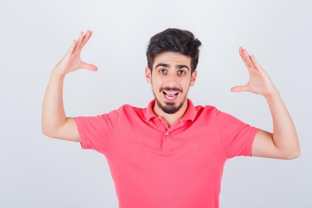 Junger mann, der sich bereit macht, den kopf im rosa t-shirt zu umklammern und glücklich zu schauen, vorderansicht.
