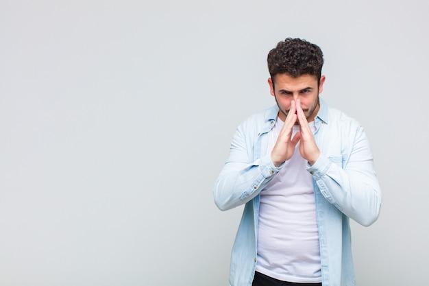 Junger mann, der sich besorgt, hoffnungsvoll und religiös fühlt, treu mit gepressten handflächen betet und um vergebung bittet