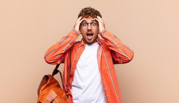Junger mann, der sich entsetzt und geschockt fühlt, die hände zum kopf hebt und bei einem fehler in panik gerät. studentenkonzept