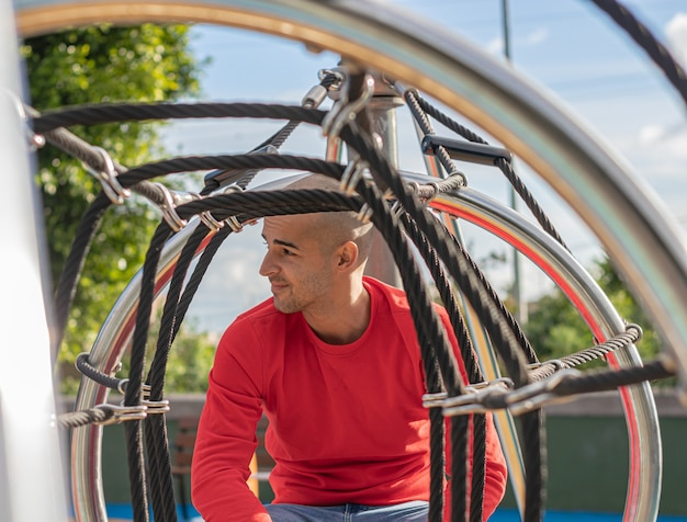 Junger mann, der sich entspannt und im park spaziert, das leben genießt und am nachmittag lächelt