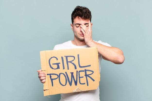 Junger mann, der sich frustriert gelangweilt fühlt und ein plakat mit dem text hält: frauenpower
