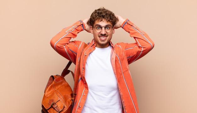 Junger mann, der sich gestresst, besorgt, ängstlich oder ängstlich fühlt, mit den händen auf dem kopf und bei einem fehler in panik gerät. studentenkonzept