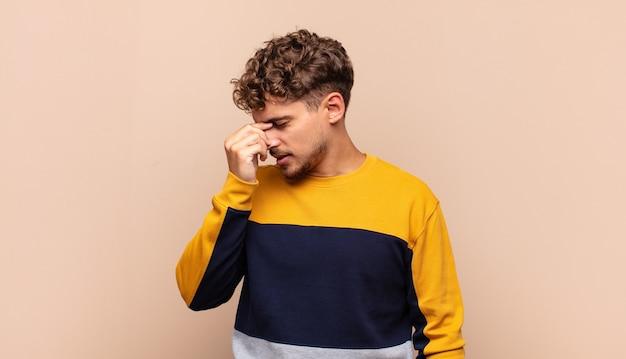 Junger mann, der sich gestresst, unglücklich und frustriert fühlt, die stirn berührt und unter migräne oder starken kopfschmerzen leidet