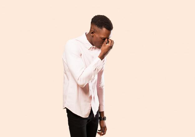 Junger mann, der sich gestresst, unglücklich und frustriert fühlt, stirn berührt und migräne von starken kopfschmerzen gegen beige wand leidet