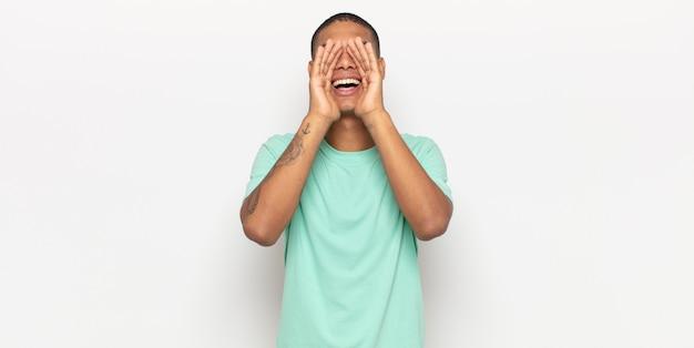 Junger mann, der sich glücklich, aufgeregt und positiv fühlt, einen großen schrei mit den händen neben dem mund gibt und ruft
