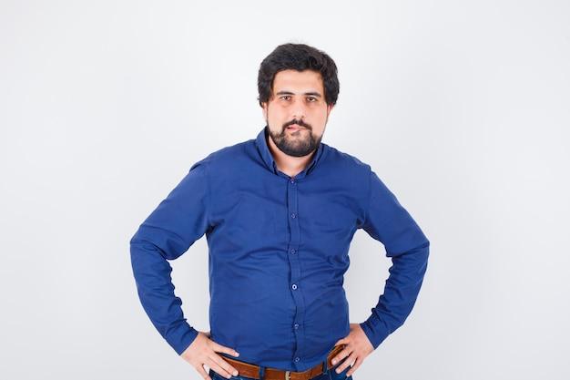 Junger mann, der sich im königsblauen hemd auf die lippe beißt und gierig aussieht, vorderansicht.