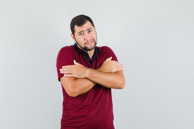 Junger mann, der sich im roten t-shirt umarmt und gekühlt sieht, vorderansicht.