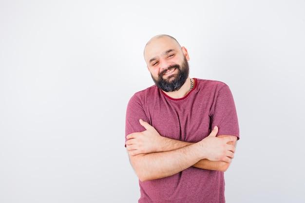 Junger mann, der sich in rosa t-shirt umarmt und glücklich aussieht. vorderansicht.