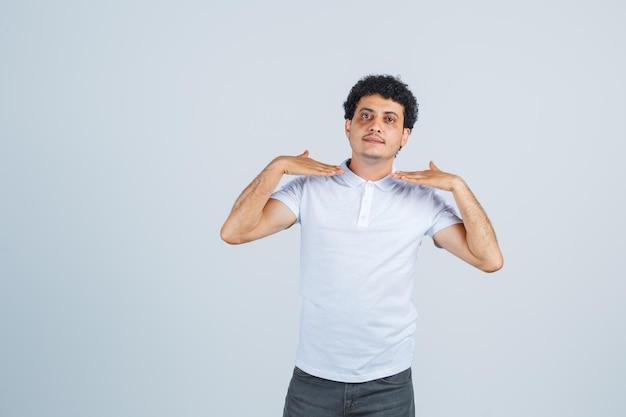 Junger mann, der sich mit händen in weißem t-shirt, hose zeigt und stolz aussieht, vorderansicht.