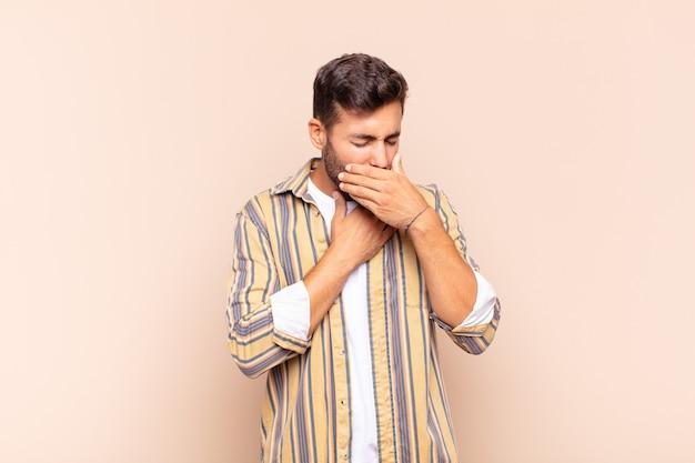 Junger mann, der sich mit halsschmerzen und grippesymptomen krank fühlt, husten mit bedecktem mund
