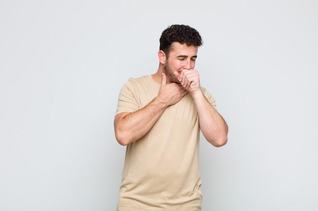 Junger mann, der sich mit halsschmerzen und grippesymptomen krank fühlt und mit bedecktem mund hustet