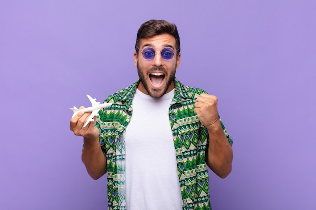Junger mann, der sich schockiert, aufgeregt und glücklich fühlt, lacht und erfolg feiert und wow sagt!. urlaubskonzept