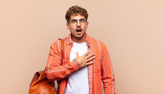 Junger mann, der sich schockiert, erstaunt und überrascht fühlt, mit der hand auf der brust und dem offenen mund und sagt, wer, ich?. studentenkonzept