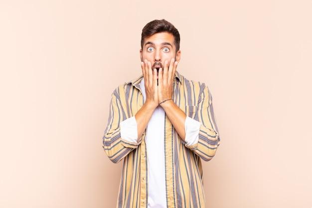 Junger mann, der sich schockiert und verängstigt fühlt und mit offenem mund und händen auf den wangen erschrocken aussieht