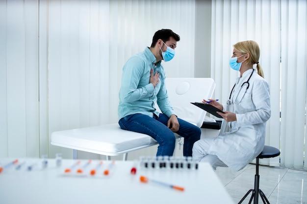 Junger mann, der sich über brustschmerzen beschwert, während arzt symptome im krankenhausbüro aufschreibt.
