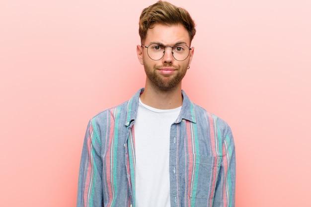 Junger mann, der sich verwirrt und zweifelhaft fühlt, sich wundert oder versucht, eine entscheidung gegen die rosa wand zu treffen oder zu treffen