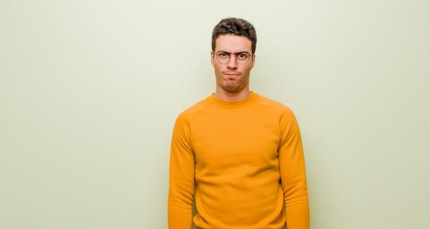 Junger mann, der sich verwirrt und zweifelhaft fühlt, sich wundert oder versucht, eine entscheidung gegen eine flache wand zu treffen oder zu treffen