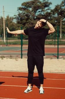 Junger mann, der sich vor dem sport im schulstadion aufwärmt